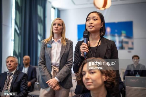 female executive asking some questions during a launch event - launch event imagens e fotografias de stock