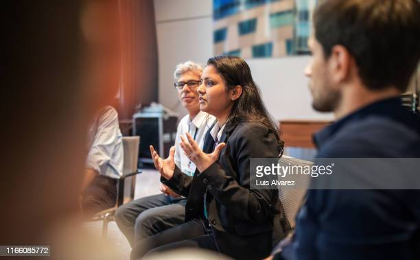 female executive explaining strategy to colleagues in seminar - differential focus stock pictures, royalty-free photos & images