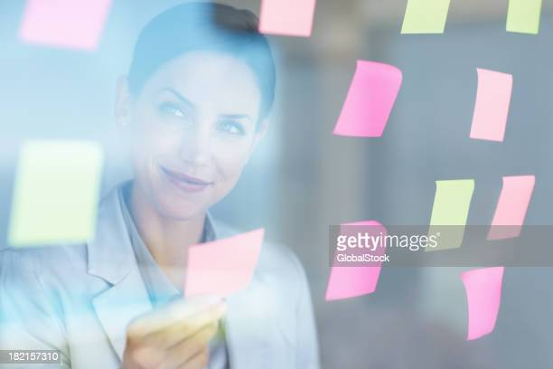 Female executive holding a sticky note