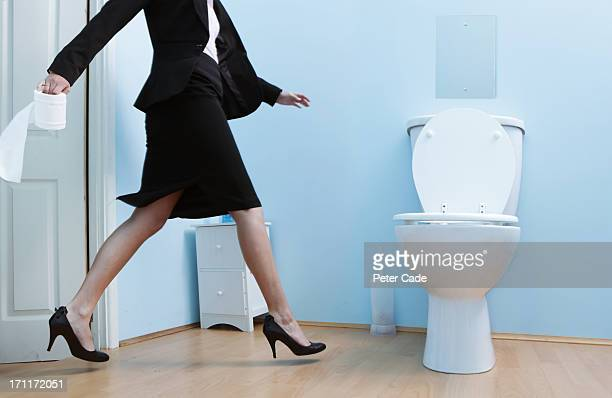 Female executive running to the toilet