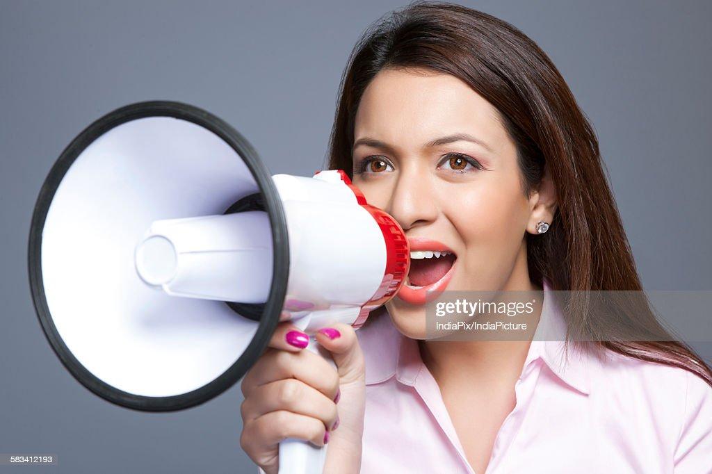 Female executive shouting through megaphone : Stock Photo