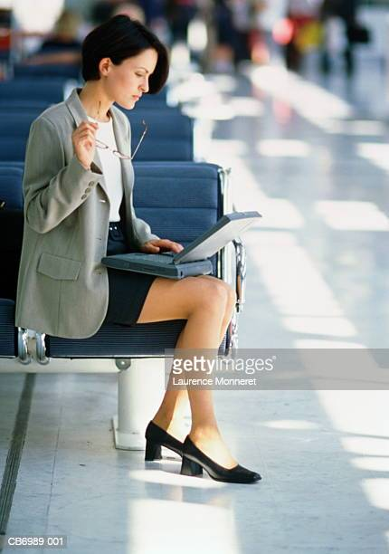 Female executive sitting in airport lounge, using laptop computer