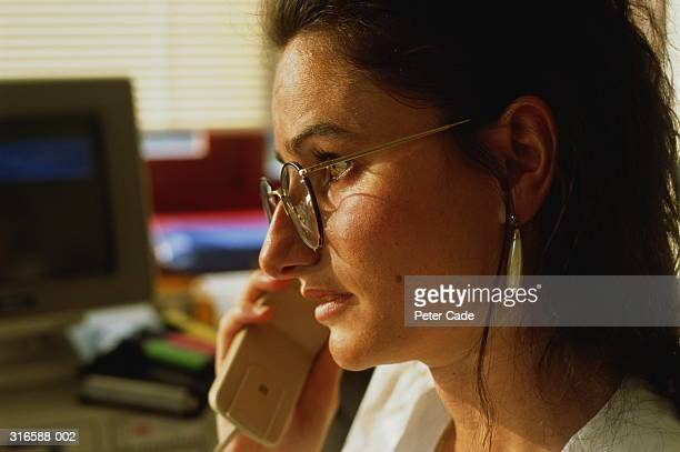 Female executive speaking on telephone,computer in background
