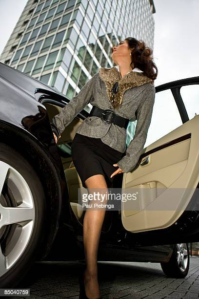female executive stepping out of car