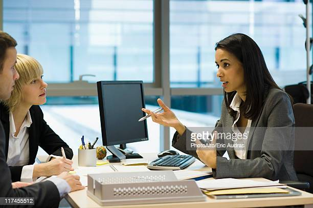 female executive talking to colleagues - bank financial building stock pictures, royalty-free photos & images