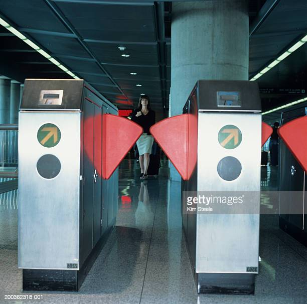 Female executive travelling at airport, red metro turnstile