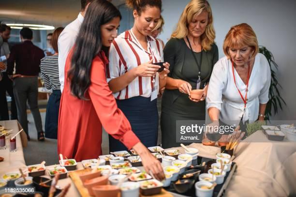 cadres féminins faisant des sélections gastronomiques de nourriture à la partie - soirée de lancement photos et images de collection
