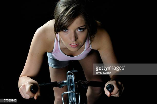 female exercising on a bike - spinning stock pictures, royalty-free photos & images