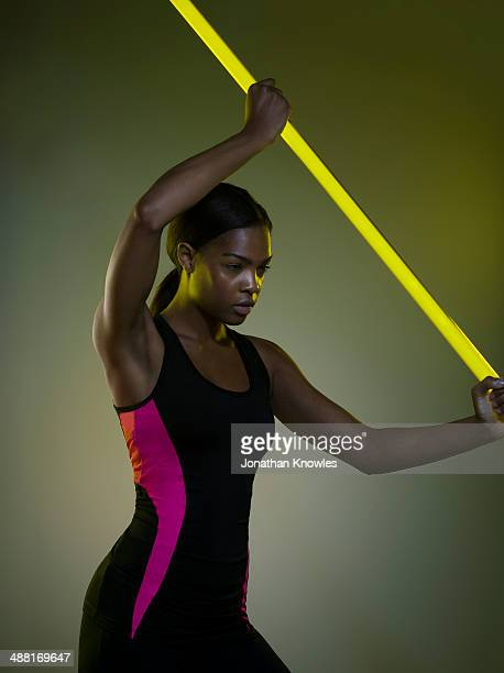 female exercising with a neon light stick - martial arts stock pictures, royalty-free photos & images