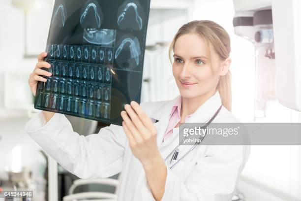 Female expert looking at dental x-ray image