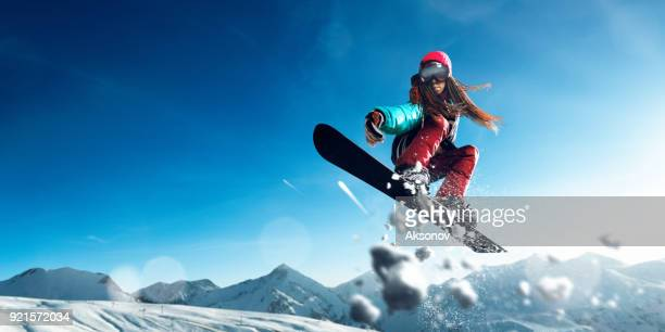 Female extreme freestyle snowboarder jump