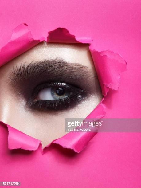 Female eye looking through paper