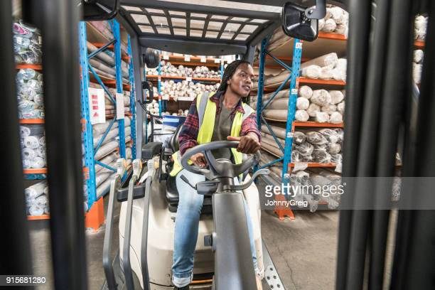 Female factory worker driving fork lift truck