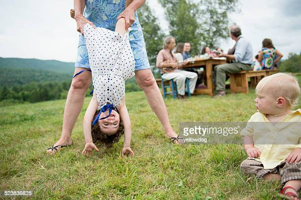 Female family member playfully holding toddler by legs at family gathering, outdoors