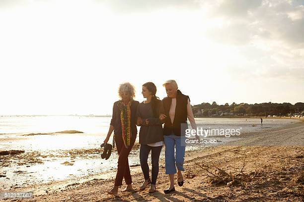 female family members walking on beach - british granny stock photos and pictures