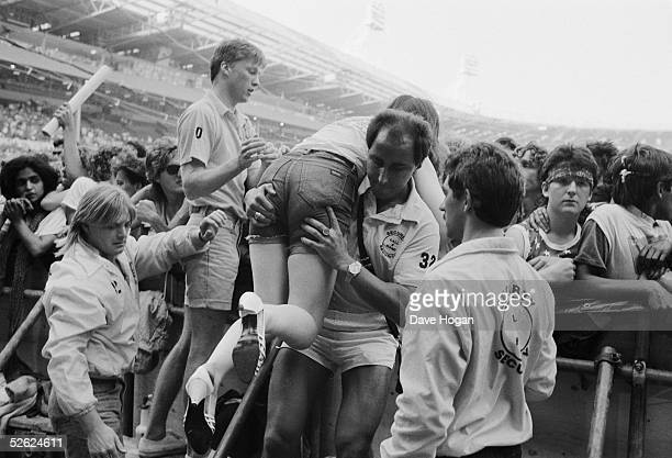 Female fan is carried out of the audience after fainting at a Bruce Springsteen concert, Wembley Stadium, 3rd July 1985.