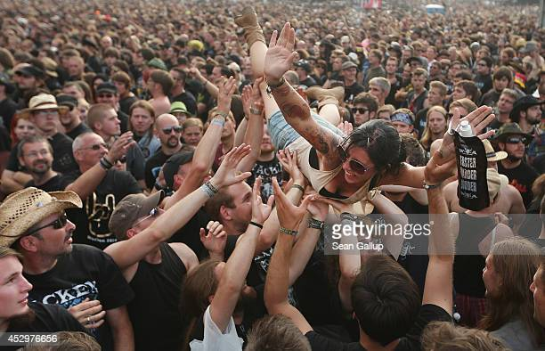 A female fan is held up by fellow fans as she floats towards the stage at the Hammerfall performance at the 2014 Wacken Open Air heavy metal music...