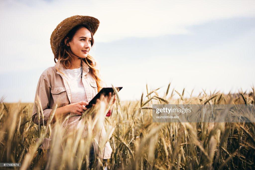 Engenheiro agrônomo da fazenda feminina verificando um campo agrícola usando um tablet : Foto de stock