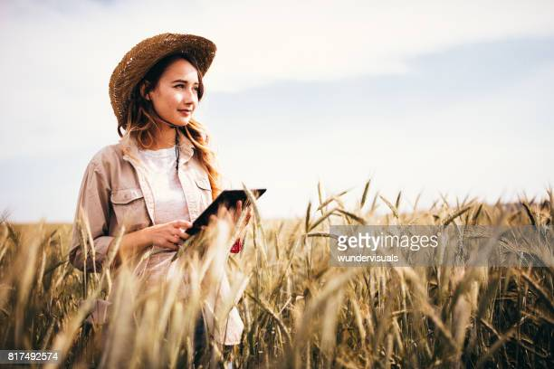 female farm agronomist checking an agricultural field using a tablet - agronomist stock pictures, royalty-free photos & images