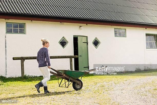 Female farm worker walking with wheelbarrow on road by barn