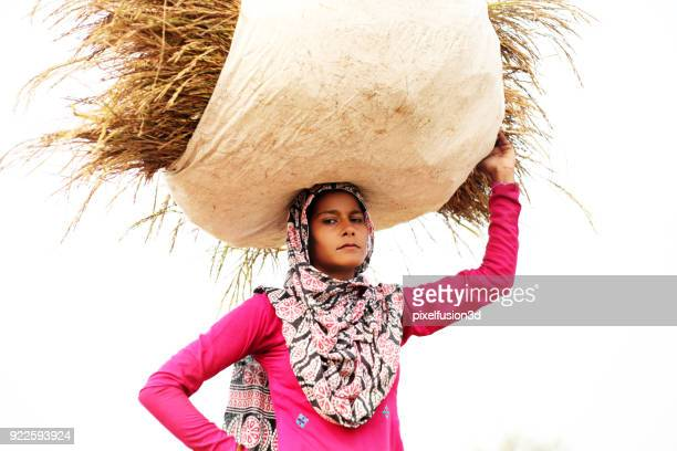 female farmer carrying grass bundle on head - indian female feet stock pictures, royalty-free photos & images