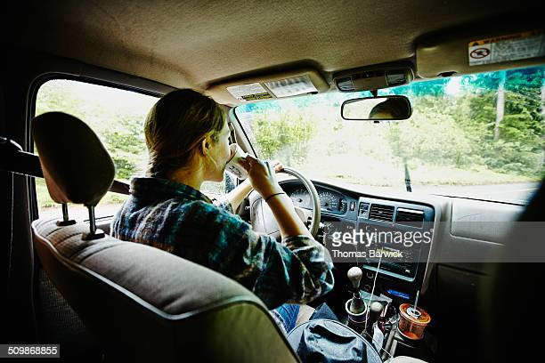 Female farmer drinking coffee in pickup truck