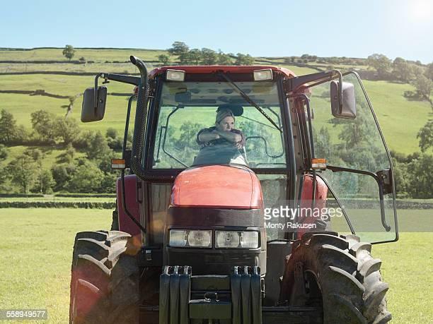 Female farmer driving tractor in field