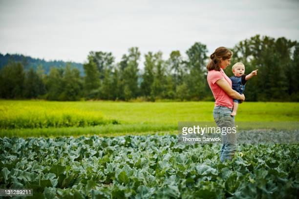 Female farmer holding baby boy in farm field