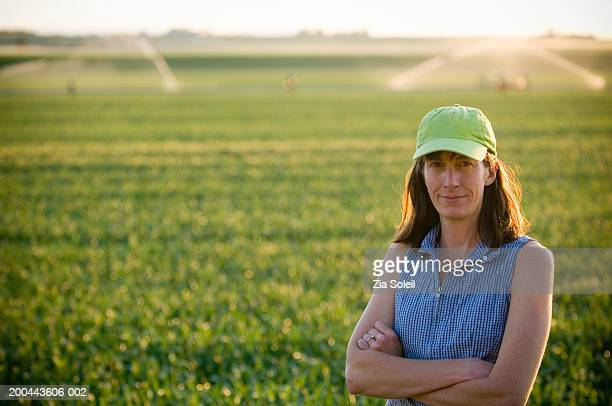 Female farmer in wheatfield, irrigation in background, summer