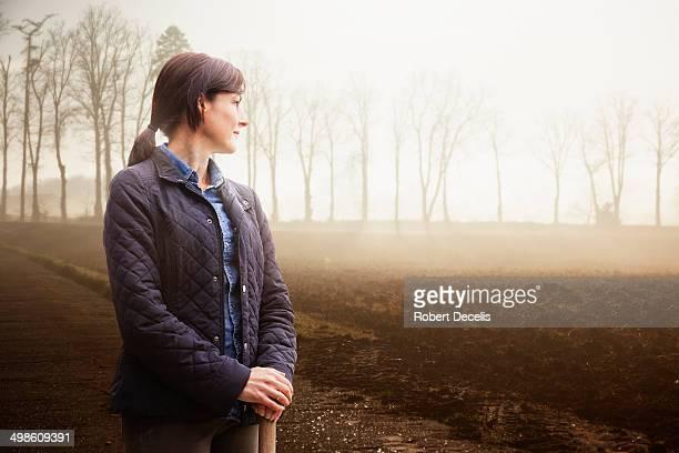 Female farmer looking over field