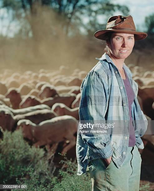 Female farmer, portrait, flock of sheep in background