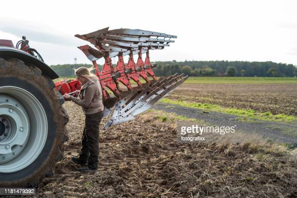 female farmer repairs a plow in a agricultural field - agricultural occupation stock pictures, royalty-free photos & images