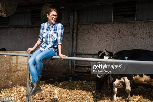 Female farmer sitting on fence at organic dairy farm