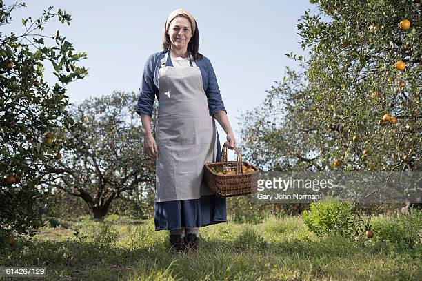 female farmer standing in orange orchard - orange orchard stock photos and pictures