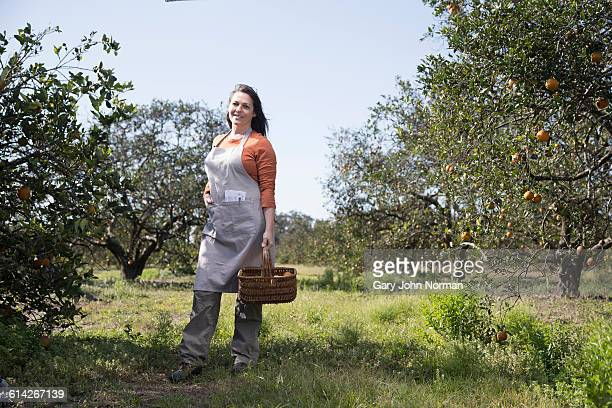 Female farmer standing in orange orchard