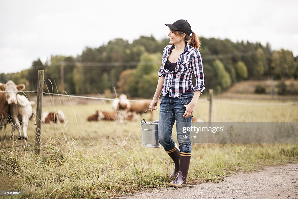 Female farmer with bucket walking while animals grazing in field : Stock-Foto