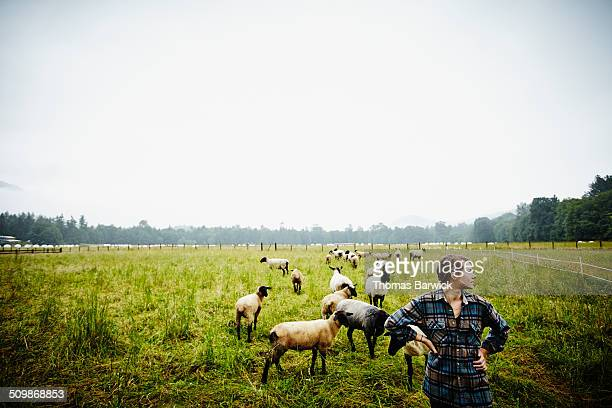Female farmer with hands on hips in pasture