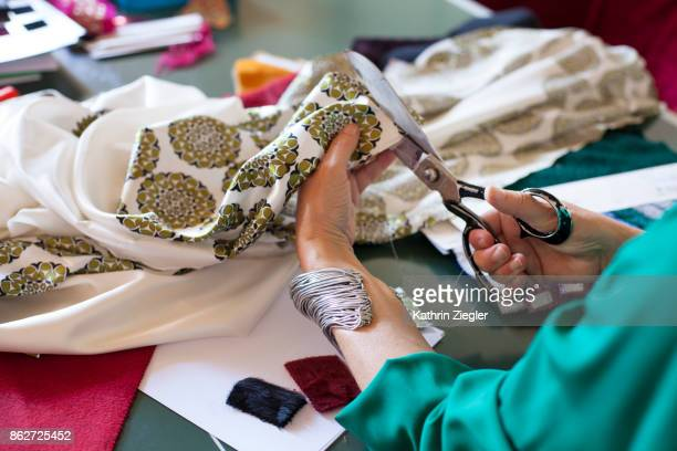 Female fashion designer at her workplace, close-up of hands cutting fabric