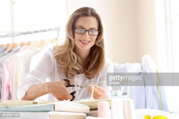 Female Fashion Designer Cutting Piece Of  Ribbon