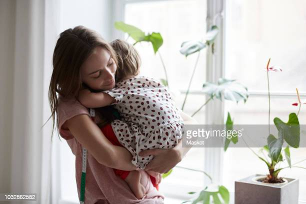female fashion designer embracing daughter while standing by window at home - aanhankelijk stockfoto's en -beelden