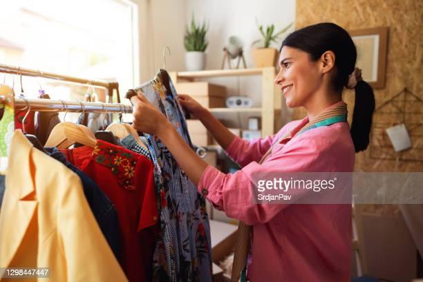 新しいオンライン注文のためのドレスを保持する女性ファッションデザイナー - デザイナー服 ストックフォトと画像