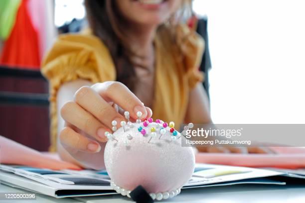 female fashion designer pick up pin at pincushion - brooch stock-fotos und bilder