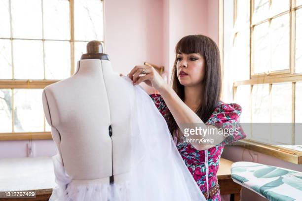 female fashion designer pinning fabric to dressmaker's model - sheer fabric stock pictures, royalty-free photos & images