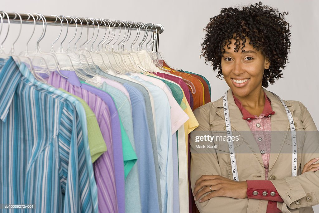 Female fashion designer standing by clothes rack, portrait : Stockfoto