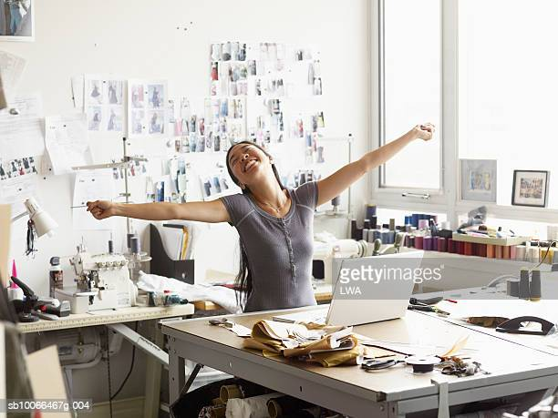 Female fashion designer stretching arms in studio, smiling