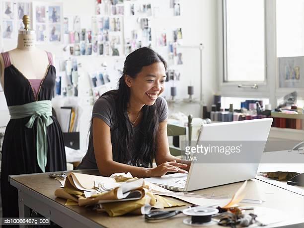 Female fashion designer using laptop in studio, smiling