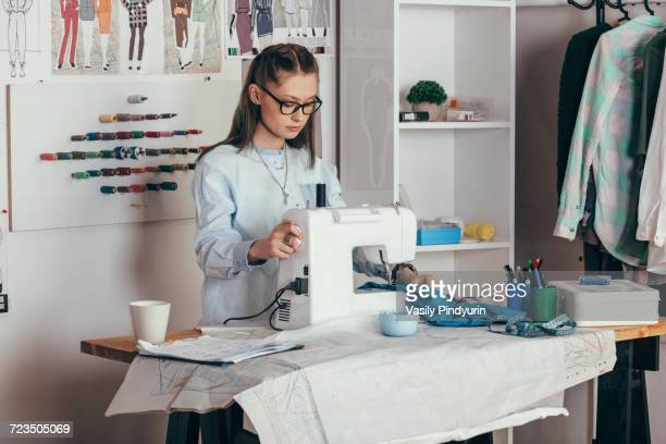 Female fashion designer using sewing machine at design studio