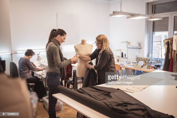 Female fashion designer with assistance in fashion design studio