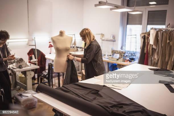 Female fashion designer with assistance in fashion design studio