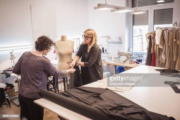 Female fashion designer working with assistance in fashion design studio